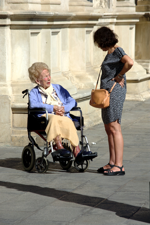 Seville, Spain, 27th September, 2016 - Urban life  - People with an invalid lady