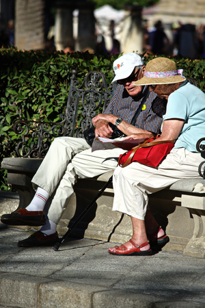 Seville, Spain, 27th September, 2016 - Urban life  - elderly couple sitting in the street Editorial