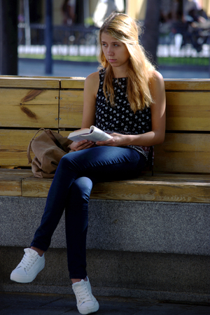 Seville, Spain, 27th September, 2016 - Urban life  - Young lady reading outdoors