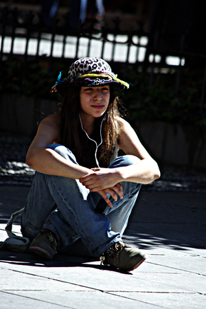 Granada, Spain, 1st October 2016, Urban life: Young lady sitting in the street