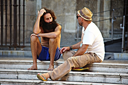 Granada, Spain, October 1st- Urban life. Two men sitting outdoors on some stairs