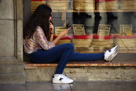 Granada, Spain, 1st October 2016 , Urban life: Young lady sitting in the street infront of a shop window Editorial
