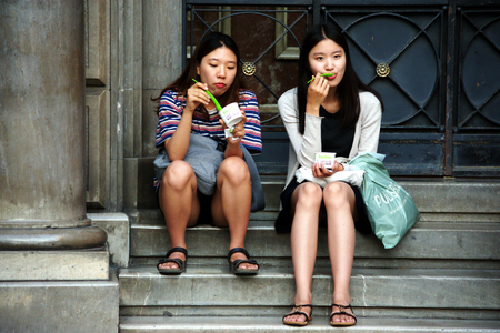 Granada, Spain, 1st October 2016 , Urban life: Eastern young ladies sitting in the street and eating Editorial