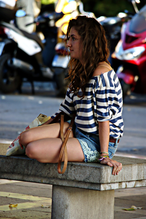 Granada, Spain, 1st October 2016- Urban life, Youing lady sitting in the street