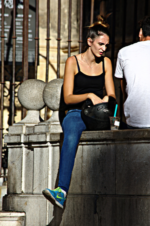 Granada, Spain, 1st October 2016- Urban life, Young lady sitting in the street
