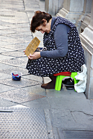 Granada, Spain, 1st October 2016- Urban life, Old lady begging in the street Editorial