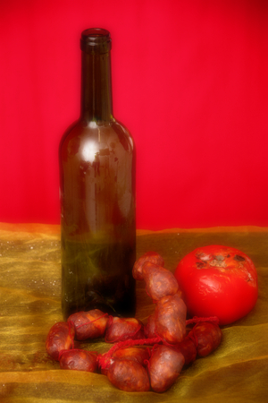 Still life with pork sausage and a bottle