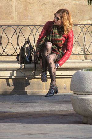 Seville, Spain, 24th January 2018 - Urban life - Young lady sitting out doors Editorial
