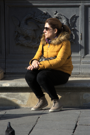 Seville, Spain, 24th January 2018 - Urban life - Young lady sitting outdoors Editorial