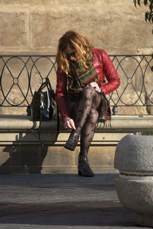 Seville, Spain, 24th January 2018 - Urban life -Young lady sitting outdoors