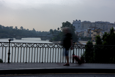 People in montion on the bridge of Triana (Seville)