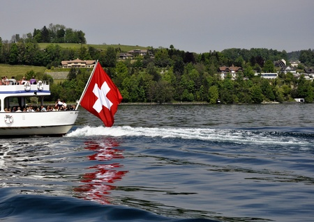 Swiss flag in boat, during summer  Lake and mountains in the back  Editorial