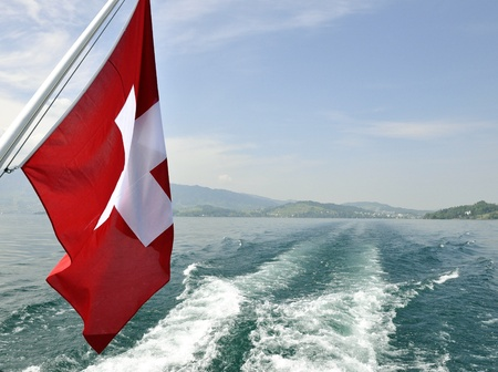 Swiss flag in boat, during summer  Lake and mountains in the back  Stock Photo