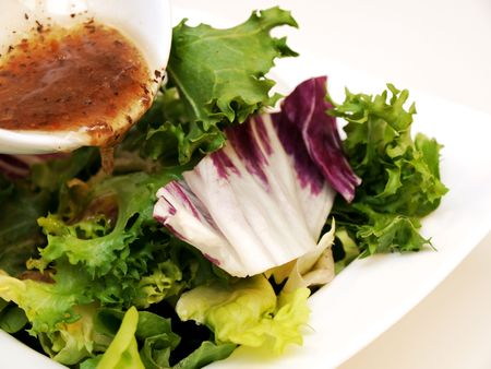 Green salad, in white bowl with italian dressing photo