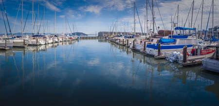 wispy: Sailboats docked at a marina, reflecting in blue water, blue sky and wispy clouds overhead.