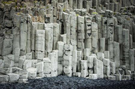 basalt: Basalt rock cliffs on a black sand beach.