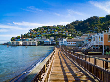 seaside town: Boardwalk leading to seaside town Stock Photo