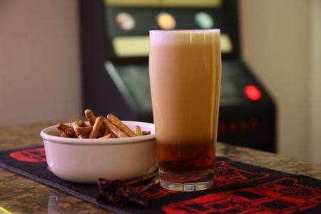 Foaming beer in pint glass next to bowl of pretzels and darts