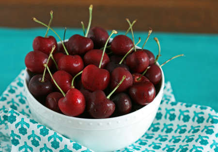 bing: Bing cherries in a white bowl, on a teal placemat Stock Photo