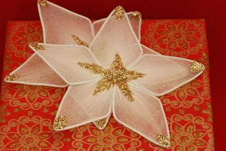 Close up of two white star Christmas ornaments on a red and gold box  Stock Photo