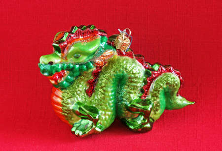 christmas dragon: Green dragon Christmas ornament on red background