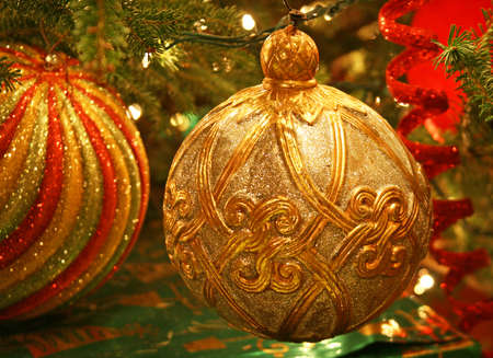Traditional gold Christmas ornament hanging on tree with other ornaments