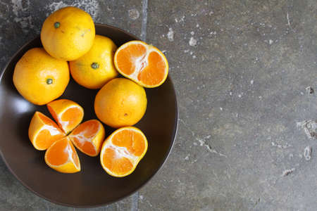 quartered: Bowl of golden-colored, seedless tangerines, whole, half and quartered, with room for text Stock Photo
