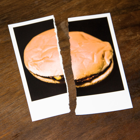 Torn Photography of a cheeseburger or hamburger Symbolizing the Renunciation of Fast Food