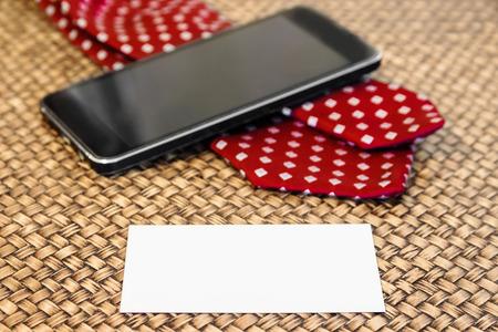 Leere Visitenkarte mit Smartphone und Krawatte im Hintergrund