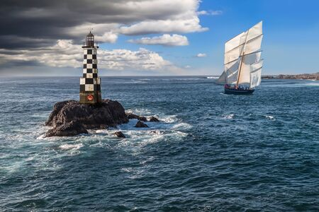 Sailboat Close to the Shore and Next to a Lighthouse with a Storm Coming Stock fotó