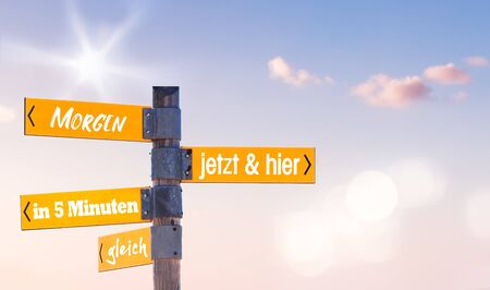 The German Words Now and Here, Tomorrow, Later and In 5 Minutes written on a Signpost