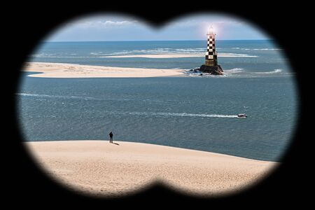Man Standing on the Beach with a Lighthouse seen through Binoculars