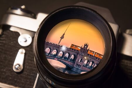 Reflection of Berlins Oberbaum Bridge in the Lens of a Vintage SLR Camera