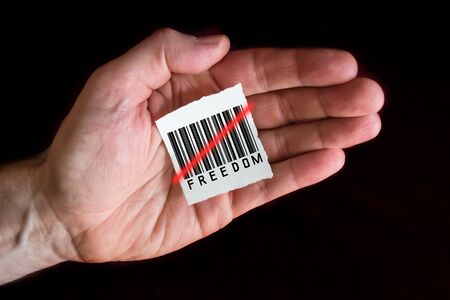 Paper Note with a Barcode that is Beeing Scanned and the Word Freedom Banque d'images