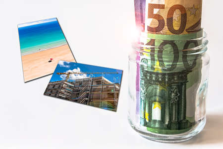 Glass Jar Filled with Euro Bankmnotes next to Photos of some Goals