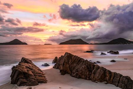 Cloudy sunrise over ocean and rocky beach