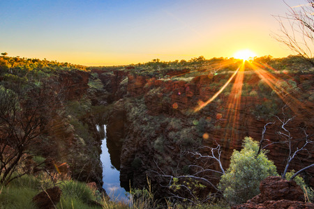 Sunrise over river flowing through outback gorge