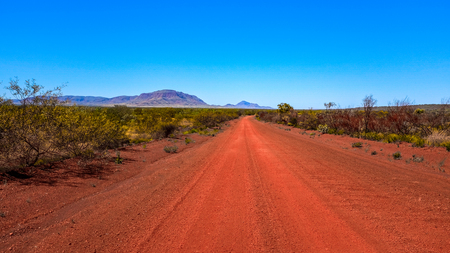 Red dirt road leading mountain and blue sky Imagens
