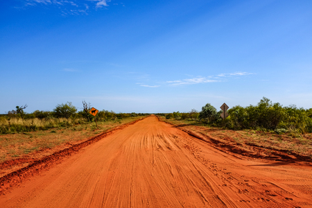 Outback red dirt road leading to horizon and blue sky