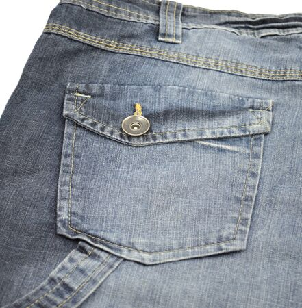 Back pocket with metal button and stitching stripe on blue jeans.