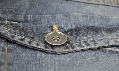Metal closeup buttom on back pocket of blue faded jeans.