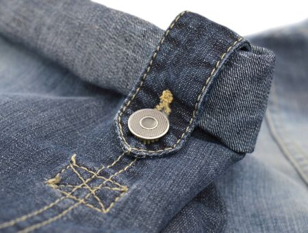 Rolled up close up blue jeans with metal button on loop stripe. Zdjęcie Seryjne