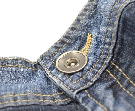 Metal button on blue jeans on belt near a fastener.