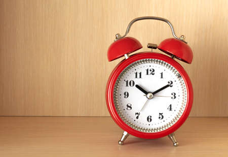 Red round alarm clock standing on shelf and shows ten hours and ten minutes.