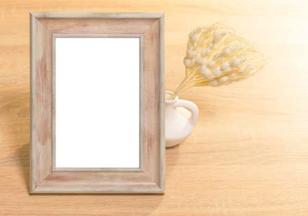 Mockup poster frame with white clay vase with dry artificial plant on wooden background with light. Stock fotó