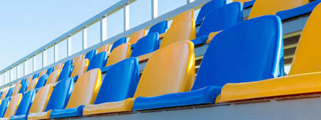 Row of yellow and blue plastic seats on stadium.