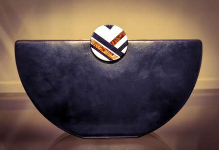 Woman's black leather clutch with round button clasp.