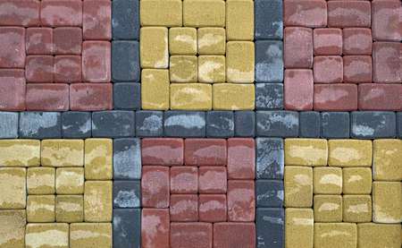 Wet tile paving slab background with red and yellow squares.