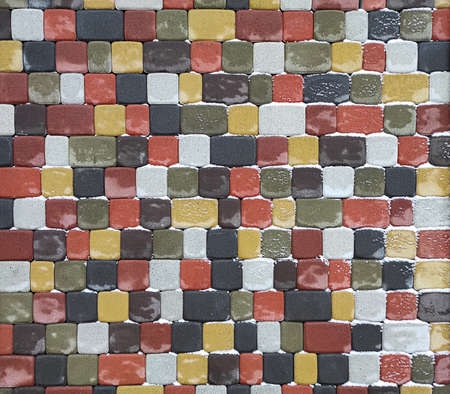 Wet tile paving slab with square color mosaic with melting snow.