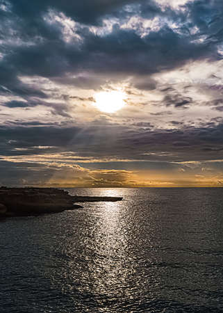 Mediterranean dark seascape on sunset with overcast clouds and sun over them.